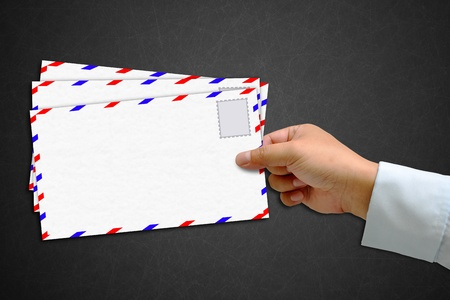 Envelope and stamp in the hand isolated on blackboard background photo