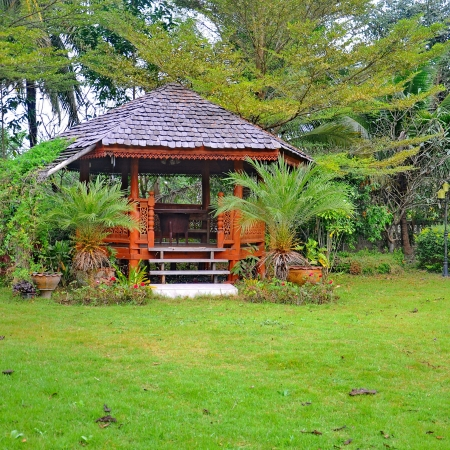 Wood pavilion in the garden on the green grass photo
