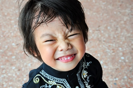 Portrait of asian boy with smile gesture and closed eyes photo