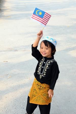 Jeune garçon tenant un drapeau de la Malaisie Banque d'images