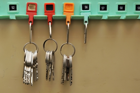 Keys with tags hanging on a wooden board Stock Photo