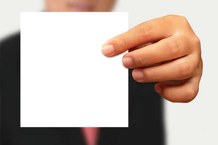 Businessman in suit showing blank paper on white background photo