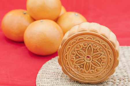 Moon cake on a bamboo mat and some oranges   photo