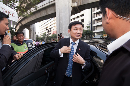 the prime minister: BANGKOK THAILAND  MARCH 22 2006 : Thaksin Shinawatra gets off a car at Era wan Shrine the Grand Hyatt Erawan Hotel Thaksin Shinawatra Prime Minister of Thailand in 2006 sees the Era wan Shrine smashed by neurotic guy.