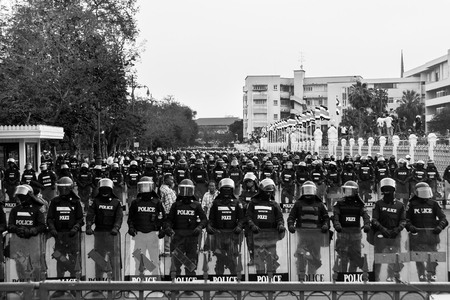 red shirt: BANGKOK THAILAND  MARCH 16 2010 : Riot polices form a line to block red shirts proterters in front of Government house during Red shirt leaders pour human blood on the gate of government house. Editorial