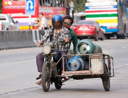sidecar: Samut Prakan, Thailand - June 2, 2015: Two men riding motorcycle sidecar carry gas tank on street