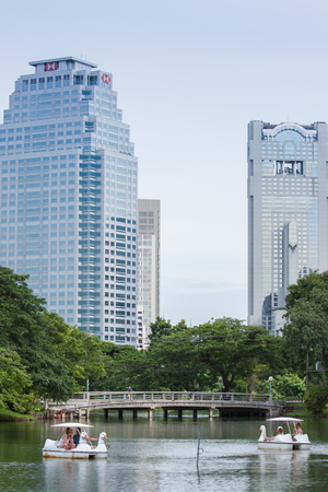 lumpini: Bangkok, Thailand - August 1, 2015: Swan Boats in Lumpini Park with skyscrapers in the background. Editorial