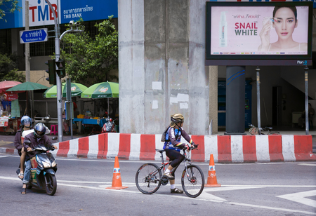 gaining: Bangkok, Thailand - July 11, 2015: Bicyclist standing with bicycle waits for green traffic light at Ratchaprasong Junction ,Cycling is gaining popularity in Thailand