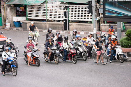 gaining: Bangkok, Thailand - June 27, 2015:  Young man standing with bicycle in front of  motorcycless row waits for green traffic light ,Cycling is gaining popularity in Thailand