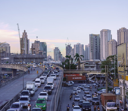 after work: Bangkok, Thailand - June 9, 2015: After work traffic jam in the evening at Na Ranong Junction with high-rise buildings in background reflecting on development of the capital