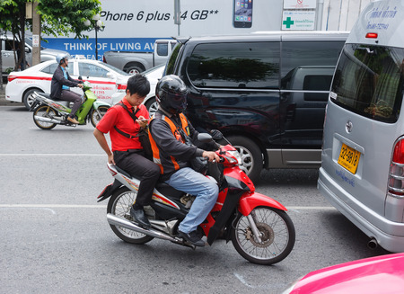 behind the scenes: Bangkok, Thailand - June 27, 2015: Young man using a smart phone while riding on pillion of motorbike taxi driving on Sukumvit Road
