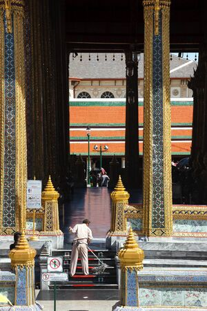 closing time: Bangkok, Thailand - June 9, 2015: An official cleans a staircase of the Emerald Buddhas temple after closing time, Grand Palace, Bangkok