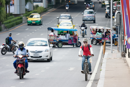 gaining: Bangkok, Thailand - June 19, 2015: A young man wearing fully protective cover rides a bicycle on street at shopping-business district. Cycling is gaining popularity in Thailand. Selective focus.
