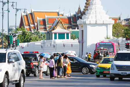 median: Bangkok, Thailand - June 9, 2015: Group of people stand on median strip to wait for crossing a street during traffic congestion near Grand Palace Bangkok