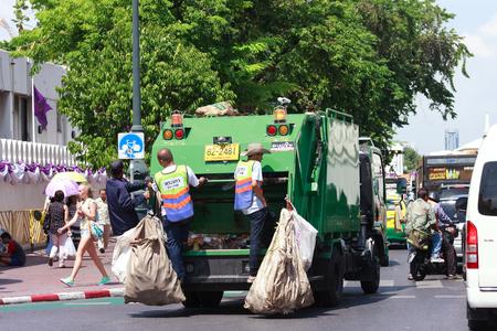 recolector de basura: Bangkok, Tailandia - 7 de junio de 2015: Camión de basura con los trabajadores de pie en la parte posterior se extiende por fuera del gran palacio el domingo para recoger la basura