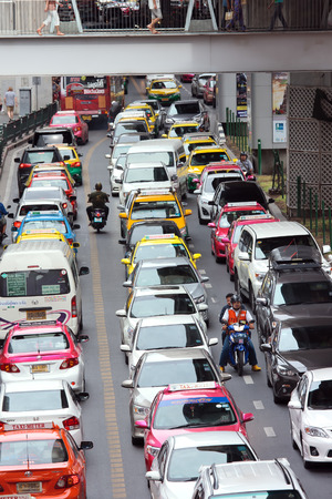rd: Bangkok, Thailand - August 1, 2015: Motortaxi and passenger get stuck in between a gap of cars during a traffic jam on Rama 1 Rd. Motorbike is the most fastest vehicles to travel in Bangkok