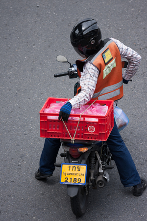 mototaxi: Bangkok, Thailand - August 1, 2015: Motorbike taxi driver checks a crates cable during stop at the red light at Sala Daeng Junction, Another job of Mototaxi is a hiring to deliver goods and documents