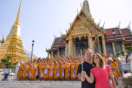 group photo: Bangkok, Thailand - June 9, 2015: Couple of tourists take a selfie while group of monks taking group photo in front of Prasat Phra Thep Bidon in Grand Palace--is the top tourist attractions in Bangkok