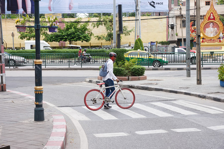 bike lane: Bangkok, Thailand - June 24, 2015: Foreigner pushing a bicycle at Asok Junction, Traveling by bike in Bangkok is a risk because some routes have no a bike lane