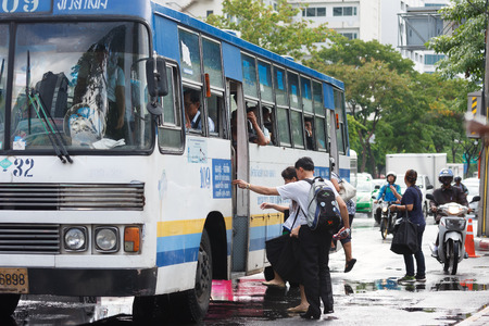 fare: Bangkok, Thailand - August 21, 2015: People getting on a bus on Rama IV Rd. after the rain, Public bus is major transportation in Bangkok because it is most covered routes and cheap fare tickets Editorial