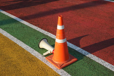 Traffic cone and megaphone on running track. The Megaphone repeatly announces a direction to Marathon runners