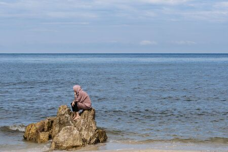 The thinker, Woman sits on a rock on Hua Hin Beach, Background