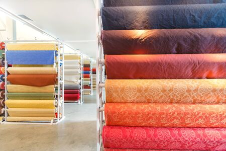 material: Colorful textile fabric material rolls in warehouse.