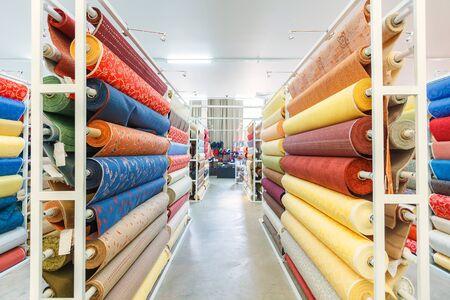 Kleurrijke textiel materiaal rollen in magazijn. Redactioneel