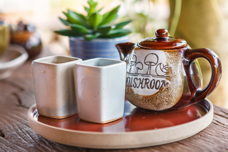 house ware: Mug and a Jug in plate on a wooden table.