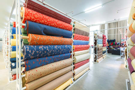 Colorful textile fabric material rolls in warehouse.
