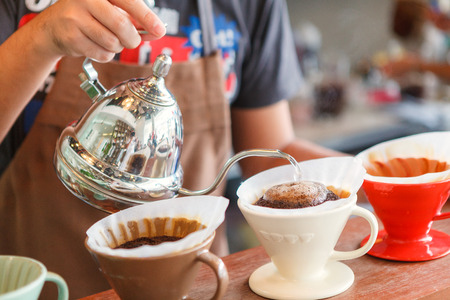 water filter: Hand drip coffee, Barista pouring water on coffee ground with filter. Stock Photo