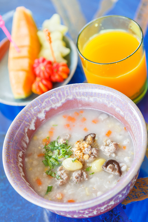 mush: Boiled rice pork or mush with orange juice and Fruit on a blue table. thai food. Stock Photo