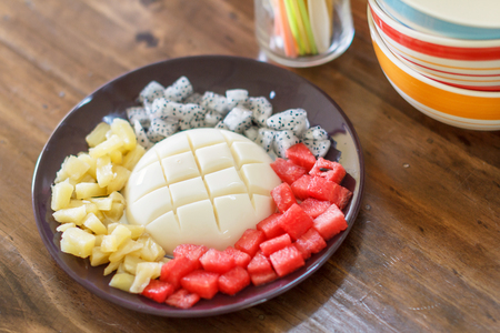 Cold tofu pudding with fruit in black plate.