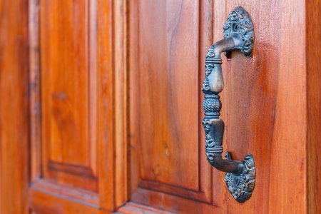 door handle: Door handle. Brown wooden door. The door handle is aluminum. Stock Photo