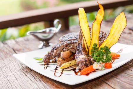 beefsteak: Grilled beefsteak on wooden table.