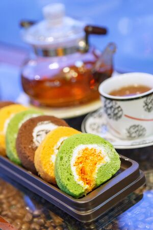 swiss roll: swiss roll with hot tea on table.