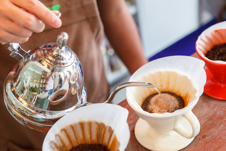 Hand drip coffee, Barista pouring water on coffee ground with filter. Фото со стока