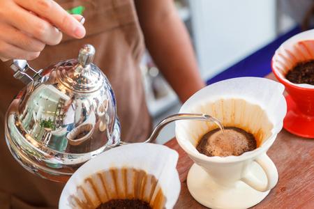 papel filtro: Mano café de filtro, Barista vertiendo agua en la planta de café con filtro.