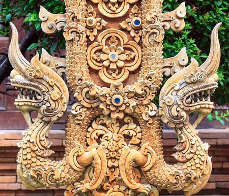 no name: Thai statue In thailand. They are treasure of buddhism. Carved stone walls for background and design. No restrict in copy or use. no name of artist appear.  Thai background. Thai design. Thai art. Stock Photo