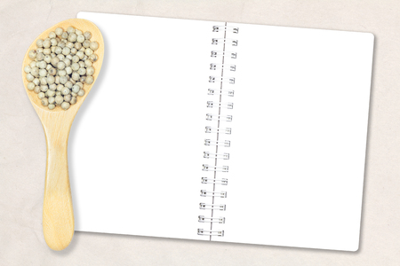 Peppercorn. White pepper in wooden spoon and notebook paper on recycled light brown paper background for design with copy space for text or image.