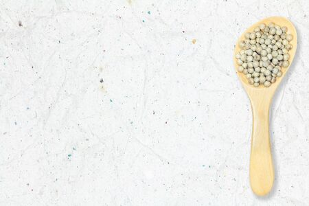 Peppercorn. White pepper in wooden spoon on recycled crumpled white paper background for design with copy space for text or image. Imagens