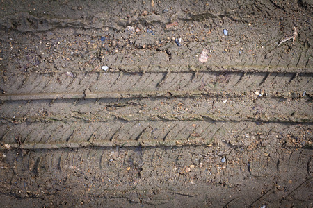 Wheel track on the soil. Track wheel on the ground. Dark edged.