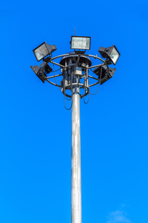 Spotlight and the sky. Spotlights lighting tower at sport arena stadium.