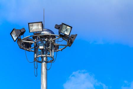 Spotlights lighting tower at sport arena stadium. Halogen spotlights and blue sky clouds.