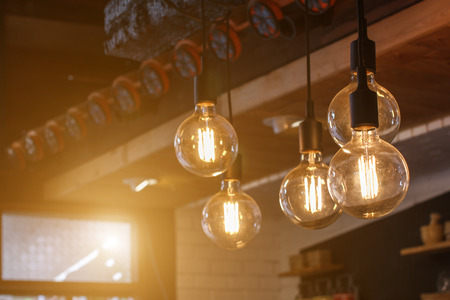 Decorative antique style filament LED light bulbs in restaurant with sunlight for electricity or technology concept design.