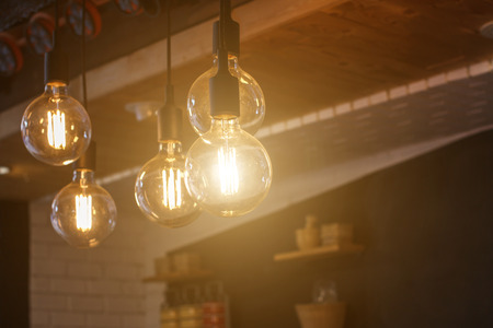 Decorative antique style filament LED light bulbs in restaurant for electricity or technology concept design. Stock Photo