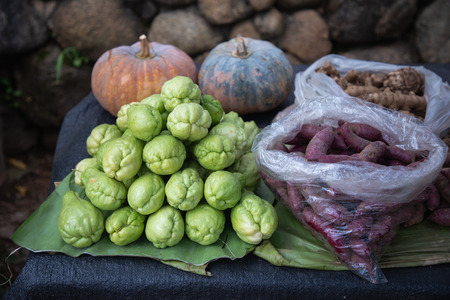 Fresh green chayote, purple yams, pumpkin and ginger on banana leaf at stall vegetable market. Stock Photo