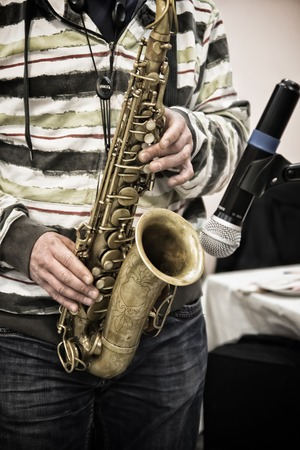 playing the saxophone next to the microphone Stock Photo
