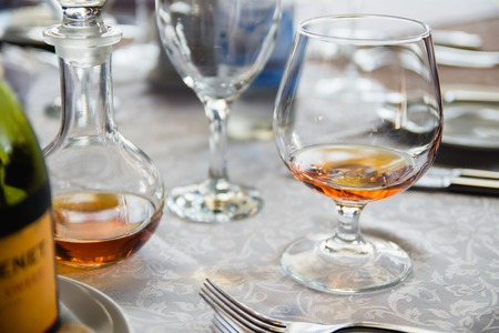 brandy: glass and decanter of brandy stood on the table Stock Photo