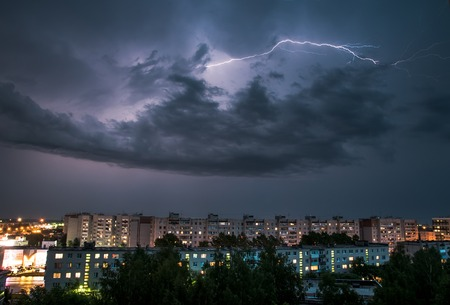 rain weather: night thunderstorm over the buildings in the city